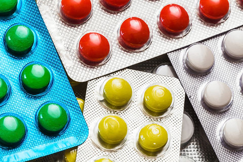 Red, green, yellow and white pills in blister packs.jpg