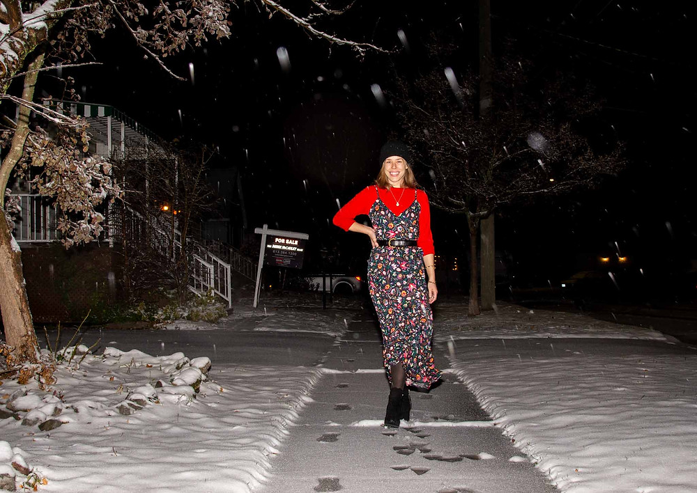 jesse smiles wide and poses with her hand on her hip on a snowy sidewalk, posing in a long floral dress with a red sweater, a black beanie and ankle boots.