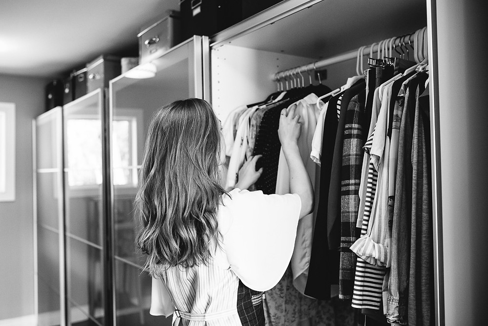 blonde woman reaching into her closet of clothing