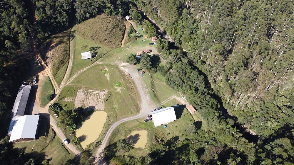 Vista da área do camping das cachoeiras com sua estrutura e cachoeira.