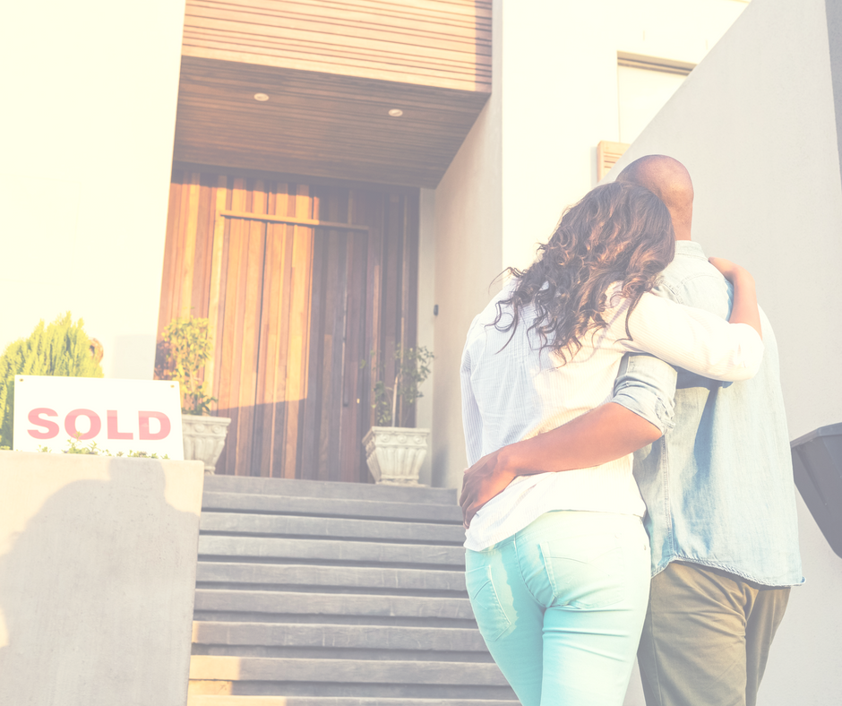 A couple standing in front of the home they just bought