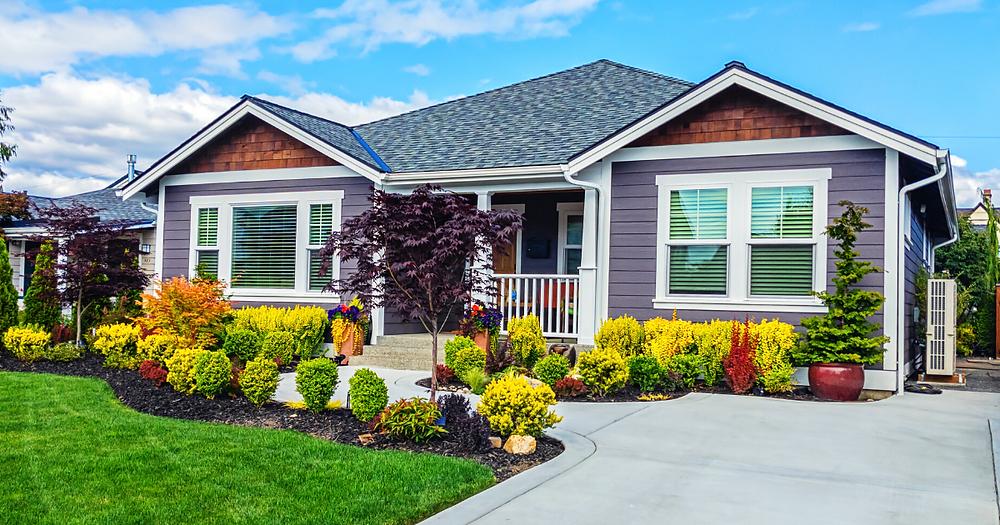 A modern custom single-level suburban home on a sunny summer day