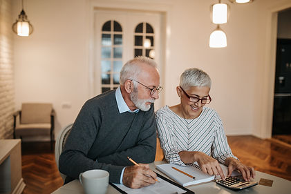 And older couple sitting at their kitchen table working on their finances