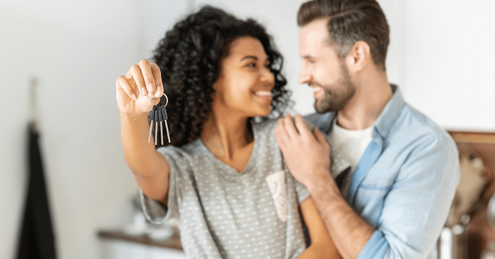 A happy young couple holding the keys to their first home