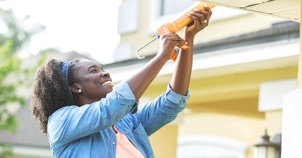 A young African-American woman standing on a ladder outside her house, using a caulk gun to repair a leak.