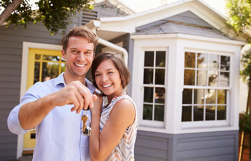 Happy couple in front of their new home holding the keys to their new home