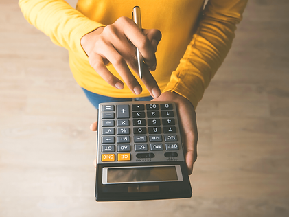 A woman in a yellow shirt using a calculator and holding a pen