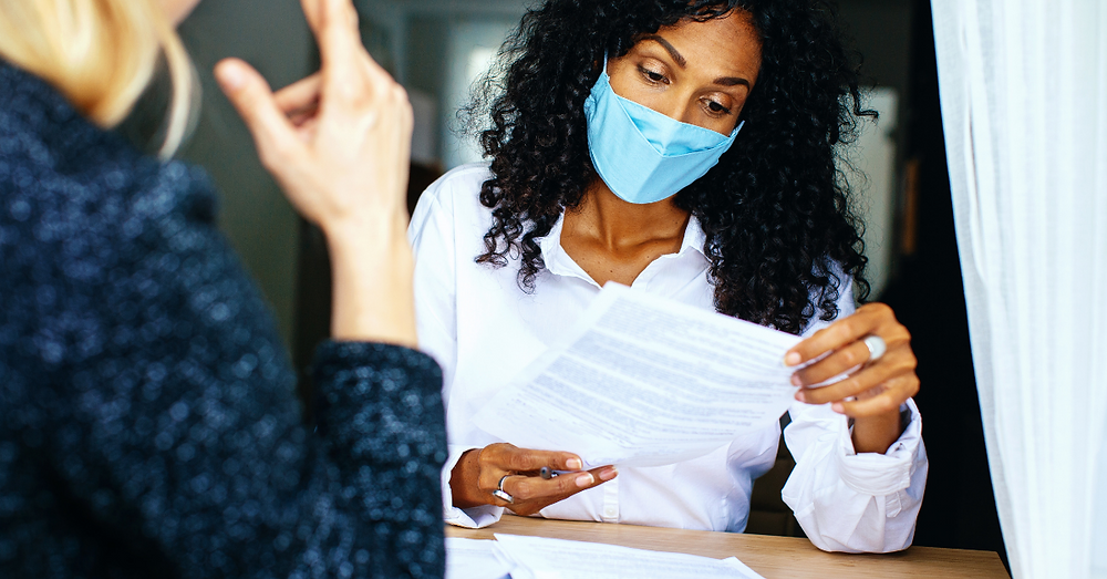 Two women looking at and reading a mortgage contract at desk with masks