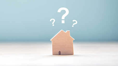 A wooden house figurine with question marks above