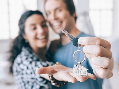 A happy couple holding the keys to their new home