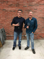 Two smiling men enjoy Viking's Landing wine