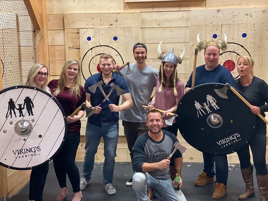 Axe throwers pose with Viking's Landing axes, helmets and shields
