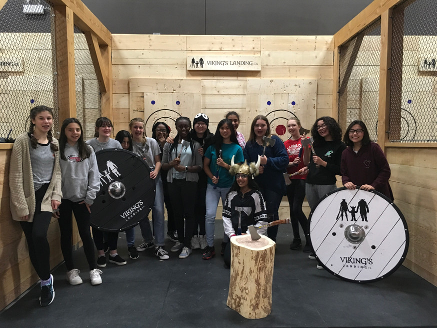 Youth axe throwers gather for photo in a Hamilton indoor axe throwing facility