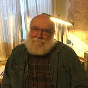 This is a headshot of Doug Newton.  Doug is bald with a full white beard and mustache.  He is wearing wire rimmed glasses and a dark tshirt. He is sitting in his office, with gold shear curtains and a desk lamp behind him.