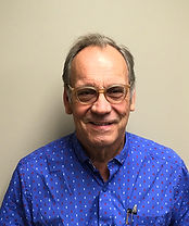 This is a headshot of Kent Ennis.  Kent has an Arizona tan, high hairline, brown eyes and wire rimmed glasses. He is wearing a bright blue button down shirt with a small white geometric patteKent is smiling for the camera. n.