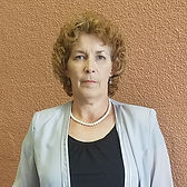 This is a headshot of Jill McCormick.  Jill has fair skin and short curly light brown hair.  She iswearing a light green jacket, black top and a pearl necklace.  She is standing against a medium brown background.