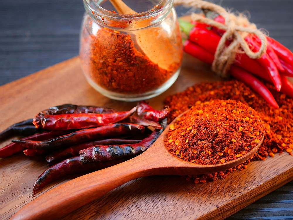 Whole and ground Cayenne pepper on a wooden chopping board