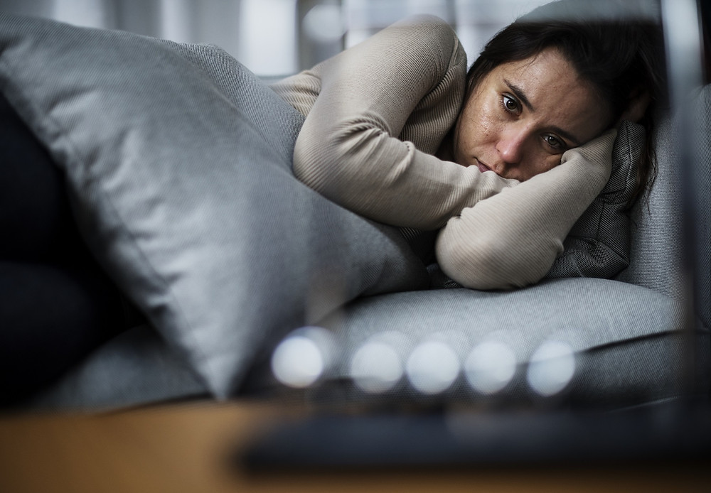 Upset brunette woman curled up on sofa