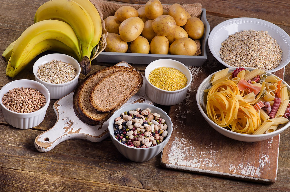 Selection of carbohydrates including bread, pasta, potatoes, nuts and bananas