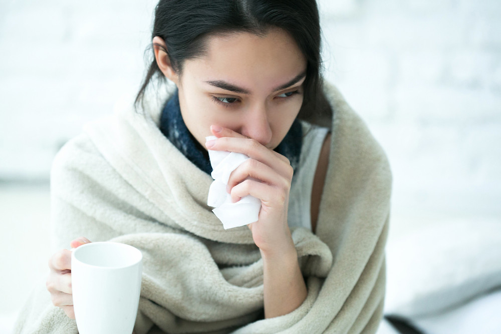 Brunette woman wrapped in blanket blowing nose into tissue