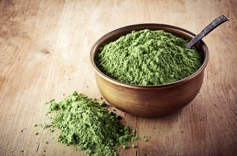 Green powered Chlorella in small bowl with teaspoon