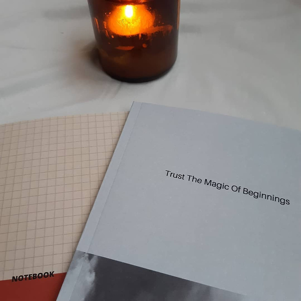 Manifestation Notebooks and a candle sitting on a white table