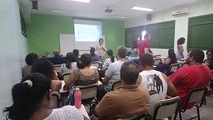 Uma sala de aula, com vários professores e a diretora Ana Paula Gulias, dando uma palestra.