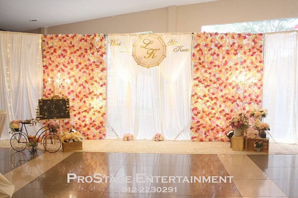 Photobooth with white curtain backdrop and flower wall