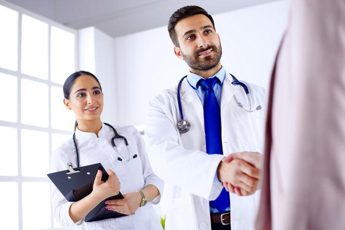 joven-medico-arabe-da-mano-paciente-hosp