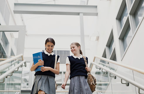 Two secondary school girls descend the stairs in a corridor, carrying brown and beige satchels on their shoulders. The girl on the left is looking down slightly, laughing. She is asian and has her black hair tied back neatly. Her friend is white and blonde haired and is looking over at her with a smile. She also haas her hair tied back. Both are wearing navy blue school vest jumpers and short sleeved white polo shirts and grey pleated skirts.