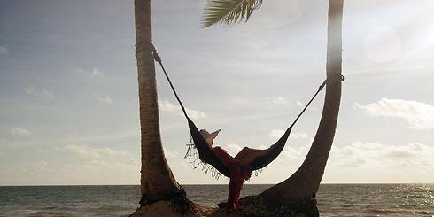 Woman lies in hammock wearing summer dre