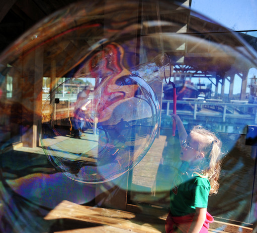 Josephine Boyd, 5, makes a giant bubble during a flash mob event at the Coos Bay Boardwalk. The event was organized by the South Coast Geocachers and was also held in 184 other countries at the same time. (The World newspaper)