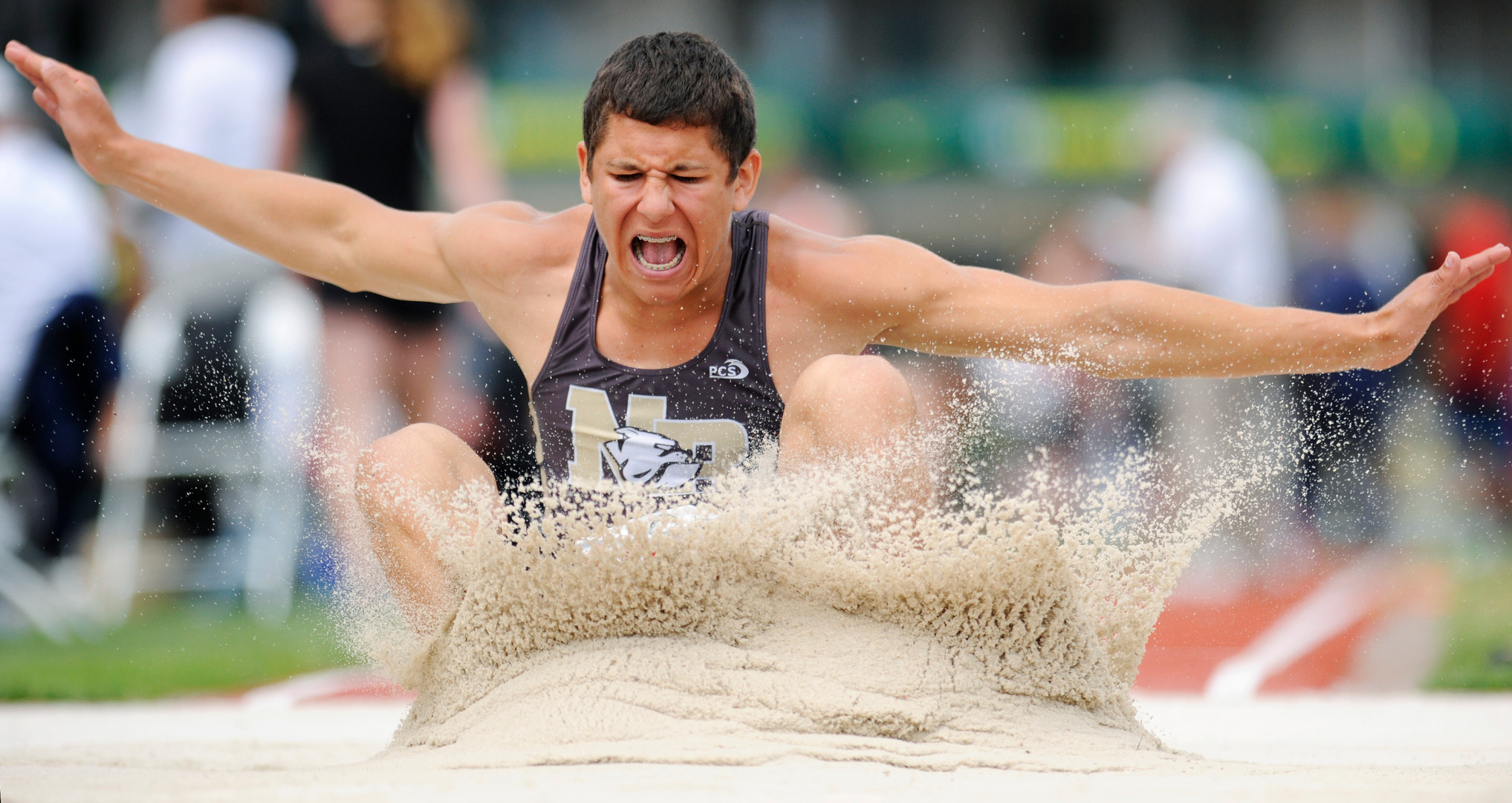 North Bend High School's Drew Matthews sends sand flying as he lands in the long jump pit Friday during the state track meet at Hayward Field in Eugene, Oregon. (The World newspaper)