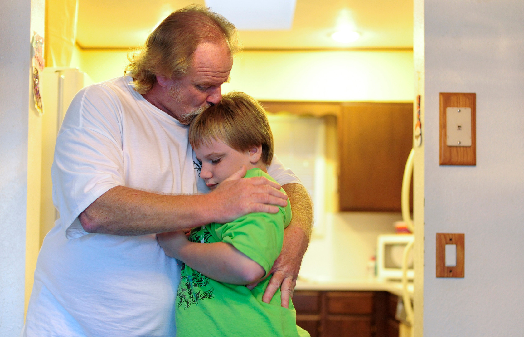 Derek Claiborne embraces his 12-year-old son Bradley who has autism. Claiborne said most kids with autism don't show much affection, but Bradley is just like a big puppy dog. (The World newspaper)