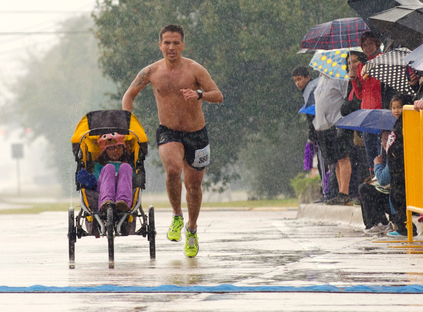 Iram Leon, 34, nears the finish line of the La Porte by the Bay Half Marathon in 10th place while pushing his daughter Kiana, 7, in a jogging stroller. Leon, from Austin, was diagnosed with terminal brain cancer four years ago. (The Houston Chronicle)