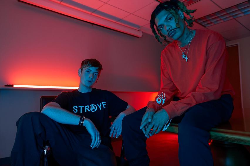 Foto de campanha da Straye. Dois homens sentados vestindo roupas da Straye.
