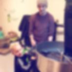 Kafferosten rostar kaffebönor medan två person tittar på