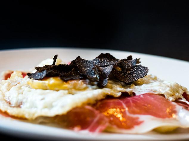 Huevos fritos trufados sobre lecho de patatas y jamón