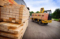 Image of lumber being moved with fork-lift truck.