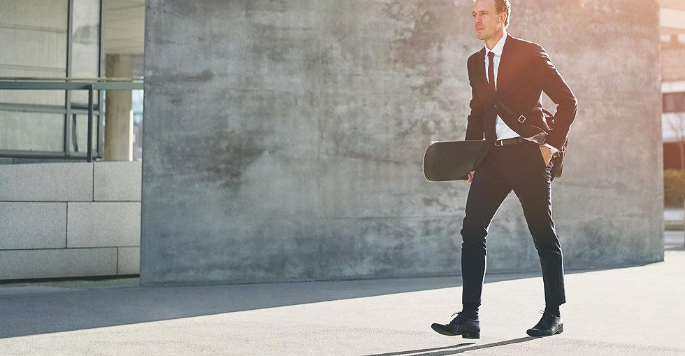 a-businessman-carries-a-skateboar1d-in-downtown-2021-08-26-17-26-35-utc copia.jpg