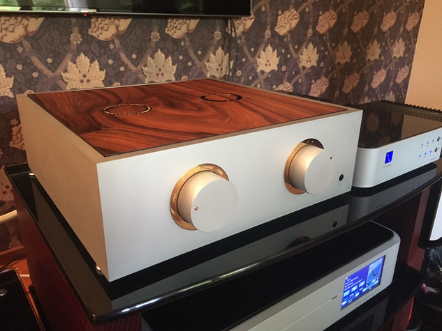 Natural pre-amplifier with gold trim and a dark burr veneer lid