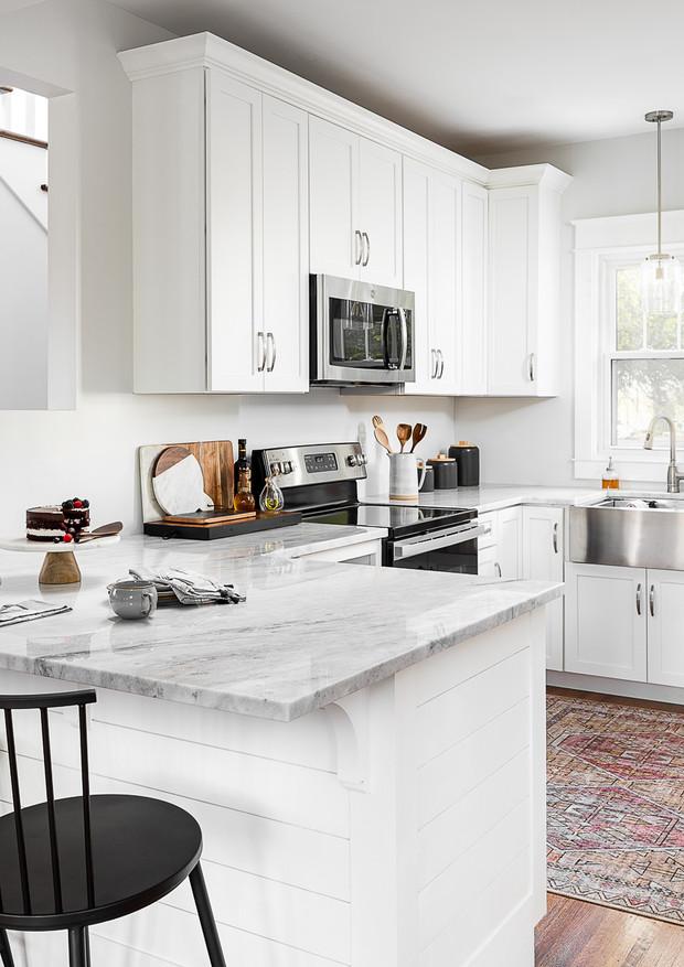 White shaker kitchen cabinets. White granite counter top. Hardwood floors in kitchen.