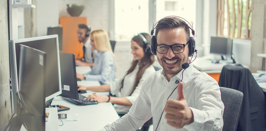 A telesales person smiles and gives a thumbs up