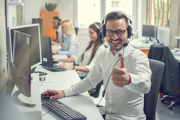 A telesales person smiles and gives thumbs up