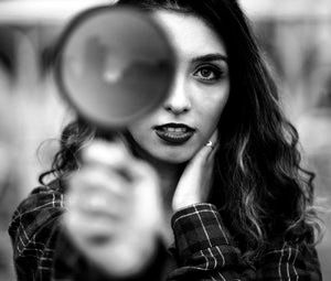 photo-of-woman-holding-magnifying-glass-