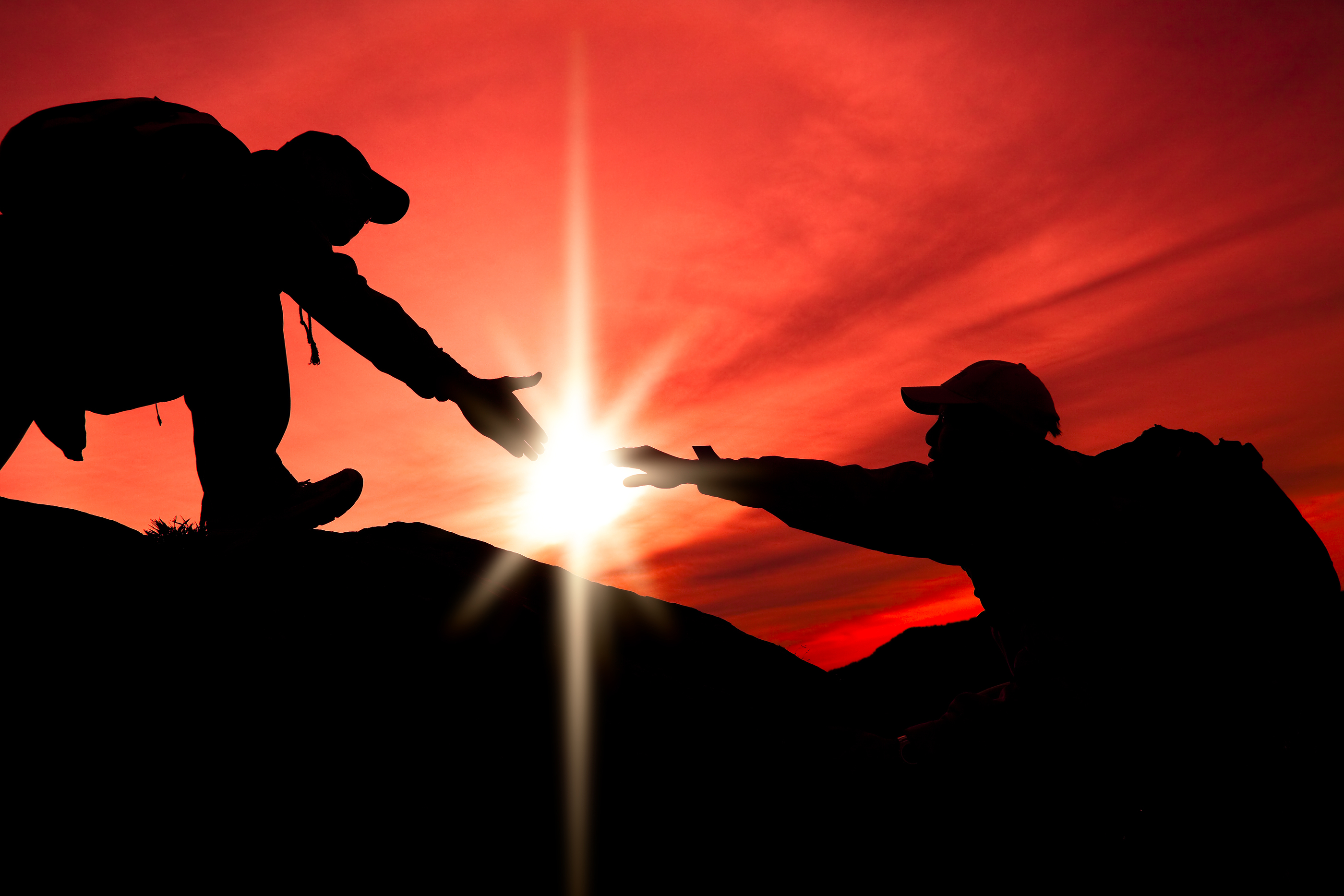 Silhouette of helping hand between two climber.jpg