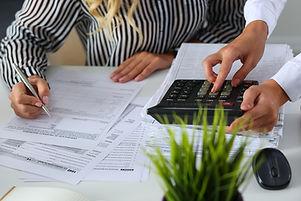 Two Female Accountants Counting On Calculator.jpg