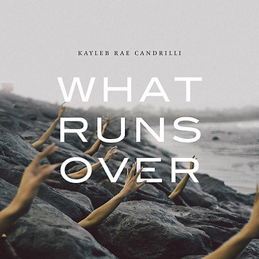 Cover of What Runs Over. Disembodied hands reaching through the crags of a rocky beach. The sky, rocks, and water are all in various hues of gray.