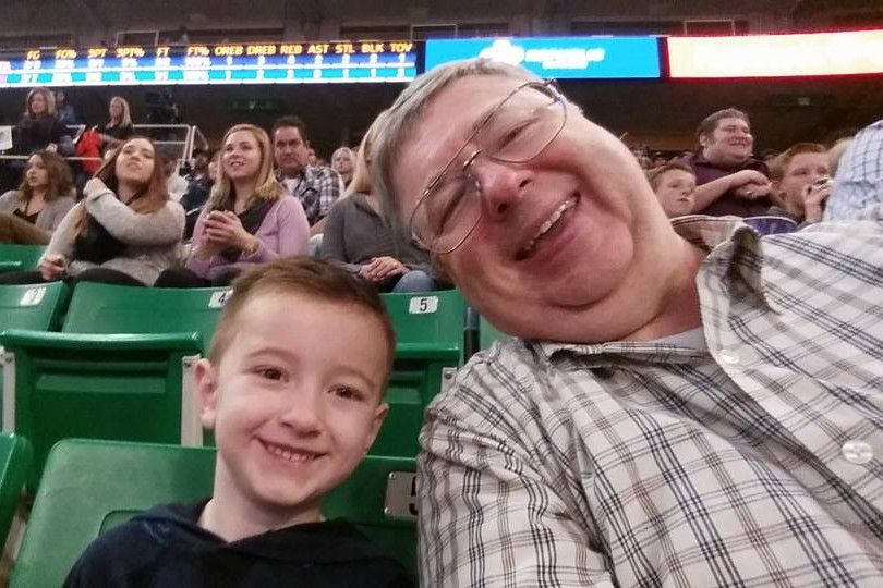 Dr. Dickson with one of his Grandsons at a Jazz Game
