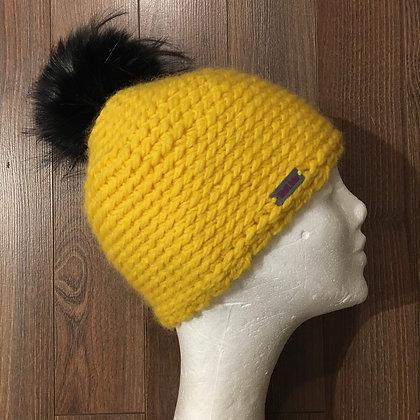 Gelbe Wollmütze mit schwarzem Bommel